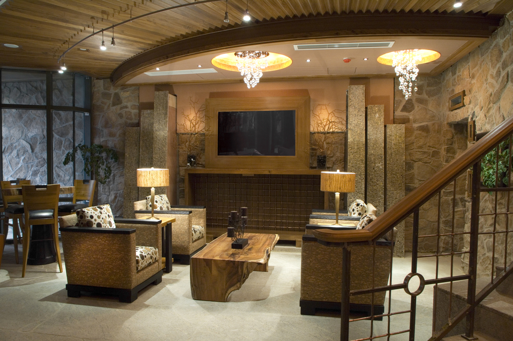 A more formal style of finished basement with sitting area, television and bar table surrounded with brick walls and wood ceiling.