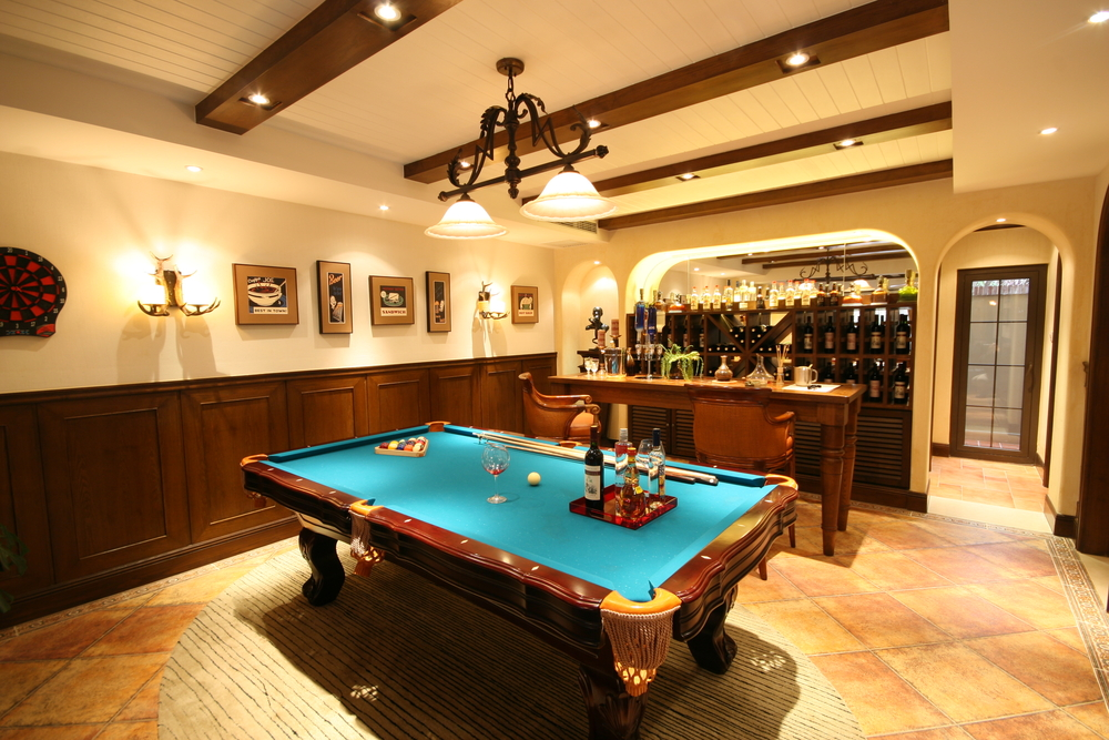 For some, the above basement is all they need – a billiard table and bar.